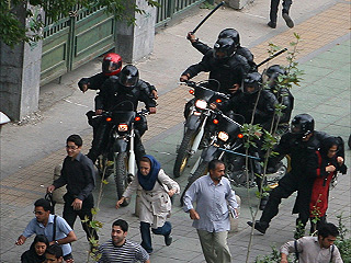 Supporters of defeated Iranian presidential candidate Mir Hossein Mousavi are followed by Iranian riot-police with batons in front of Tehran University during riots in Tehran, Iran, Sunday, June 14, 2009. (AP Photo) #