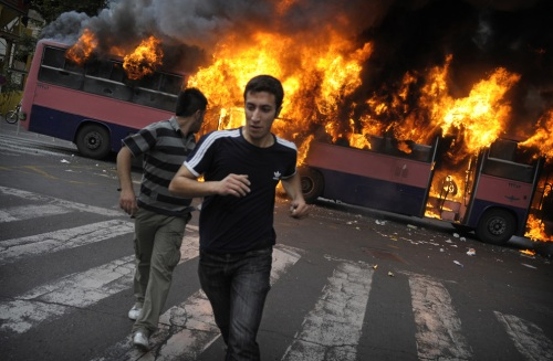 Young men run past a burning bus during a riot in Tehran on June 13, 2009. (OLIVIER LABAN-MATTEI/AFP/Getty Images) #