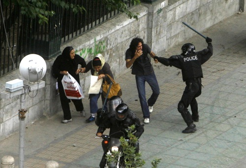 A riot-police officer strikes a man with a baton near Tehran University on June 14, 2009