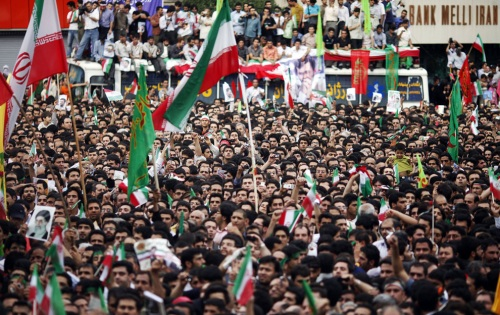 Supporters of President Mahmoud Ahmadinejad wave Iranian and religious flags during a victory celebration in central Tehran June 14, 2009. (REUTERS/Damir Sagolj)