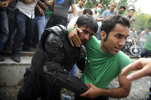 A backer of Mir Hossein Mousavi helps evacuate an injured riot-police officer during riots in Tehran on June 13, 2009. (OLIVIER LABAN-MATTEI/AFP/Getty Images) #