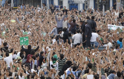 Defeated reformist presidential candidate Mir Hossein Mousavi (center) raises his arms as he appears at an opposition demonstration in Tehran on June 15, 2009, appearing in public for the first time since an election that has divided the nation.